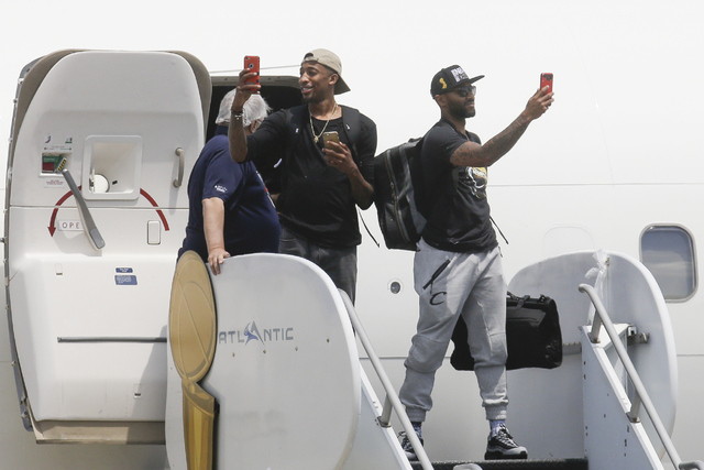 NBA champion Cleveland Cavaliers' Jordan McRae, right, and Iman Shumpert, left, take photos of a cheering crowd as they arrive at the airport Monday, June 20, 2016, in Cleveland. (John Minchillo/AP)