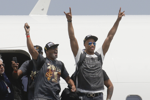 NBA champion Cleveland Cavaliers' Dahntay Jones, right, and Mo Williams celebrate as they arrive at the airport Monday, June 20, 2016, in Cleveland. (John Minchillo/AP)