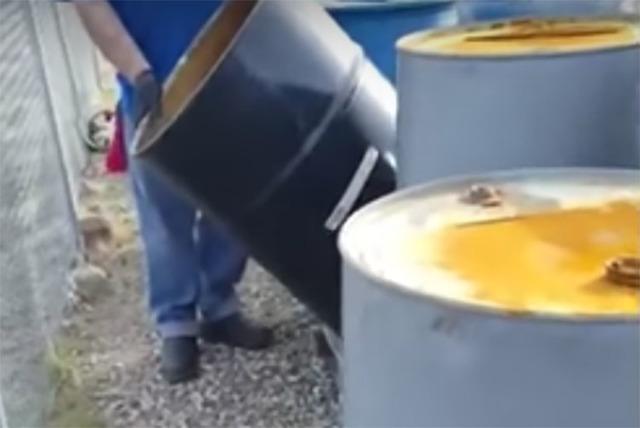 Video footage shows workers draining barrels of liquid in the Nevada desert. (Screengrab/Joseph Baylon/YouTube)