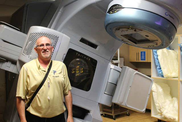 Henderson resident Sheldon McArthur, who recently went through treatment for colorectal cancer, is shown next to a radiation therapy machine inside 21st Century Oncology. Michael Lyle/View