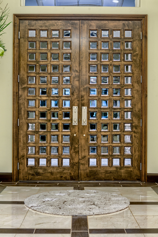 The 6½ by 9-foot custom double mahogany doors, featuring 96 4-inch square panes of tempered glass, cost $7,800. It was manufactured locally by Classic Door & Trim. (COURTESY OF LUXURY ESTATES ...