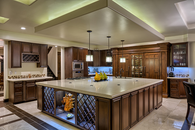 The kitchen features a 20-foot-by-20-foot center island with Italian Caesarstone Dreamy Marfil countertop, customized alder wood cabinetry and updated stainless steel Dacor appliances. (COURTESY O ...