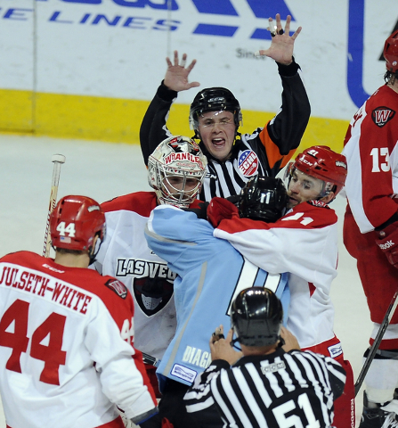 Las Vegas Wranglers defenseman Greg Coburn, center, ties up Alaska Aces left wing Tommy Mele in front of goaltender Travis Fullerton while ECHL referee Nick Leduc, center, tries to break up the sc ...