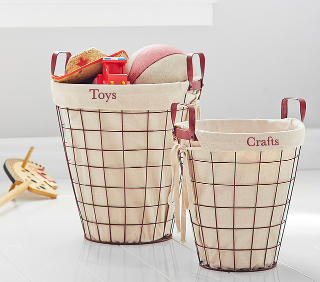 COURTESY Life with children isn't always neat and tidy, so be ready to clear the clutter quickly by depositing items into large baskets placed in shared areas. Pottery Barn Kids wire baskets with  ...