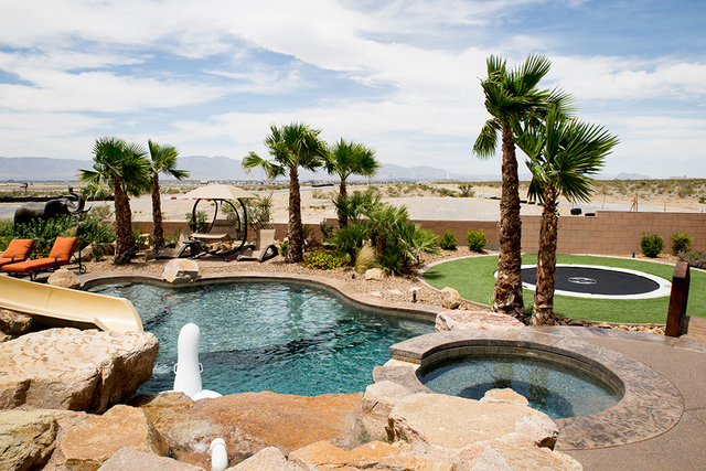 In the backyard, there's a large swimming pool with waterfall features as well as a hot tub, built-in trampoline and a small shooting range that leads into the desert. (TONYA HARVEY/REAL ESTATE  ...