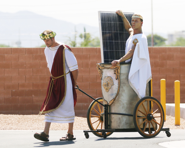Joshua Self, left, dressed as a warrior pulls a chariot carrying Chris Justis, dressed as Apollo, and a solar panel during a news conference at Cox Las Vegas on Monday, June 20, 2016, in Las Vegas ...