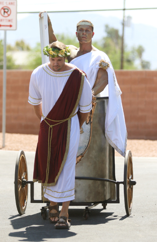 Joshua Self, left, dressed as a warrior pulls a chariot carrying Chris Justis, dressed as Apollo and a solar panel during a news conference at Cox Las Vegas on Monday, June 20, 2016, in Las Vegas. ...