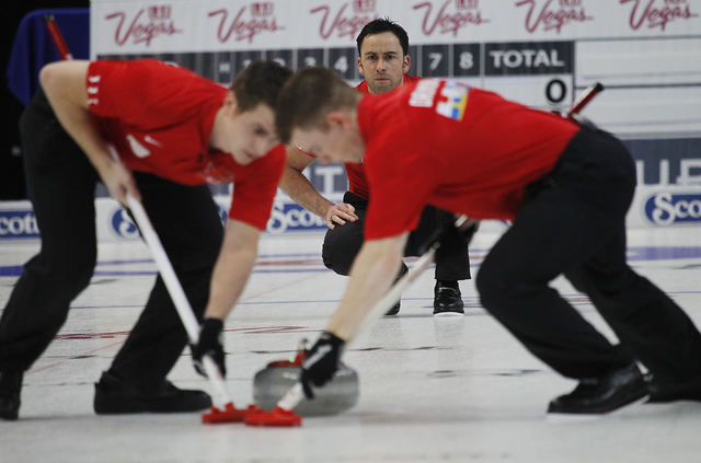 Team World's David Murdoch, in back, delivers a rock as teammates Greg Drummond, right, and Scott Andrews sweep the ice during the 2014 World Financial Group Continental Cup of Curling at the Orle ...