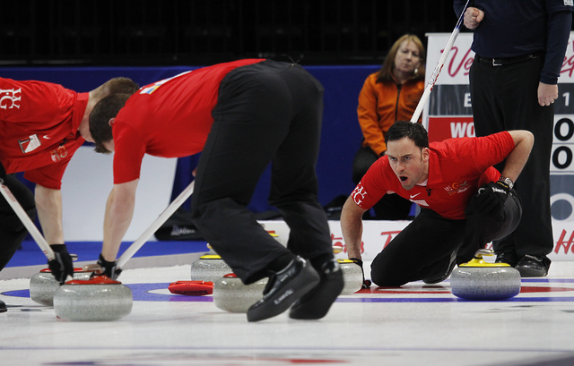 Team World's David Murdoch, far right, shouts instructions to his sweepers Greg Drummond, left, and Scott Andrews during the 2014 World Financial Group Continental Cup of Curling at the Orleans Ar ...