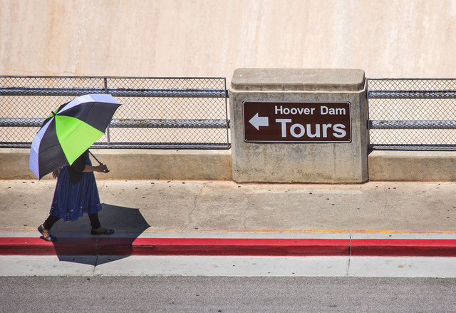A woman shades herself with an umbrella while walking past the Arizona Spillway at Hoover Dam on May 31. Jeff Scheid/Las Vegas Review-Journal Follow @jlscheid