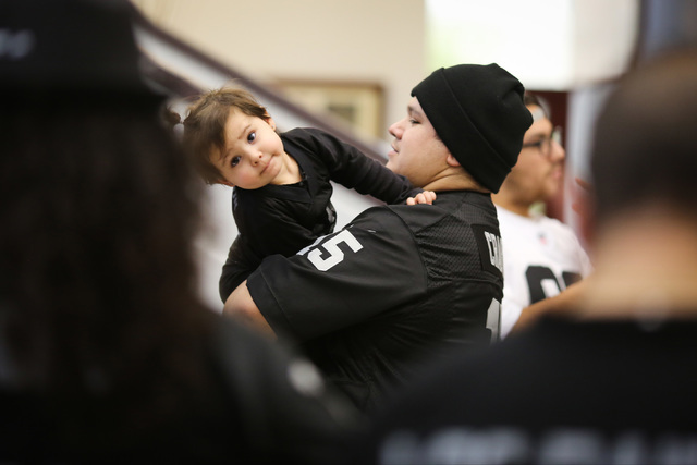 Delfina Rubi IV, 24, holds his 2-year-old daughter Penelope Rubi while waiting for Oakland Raiders owner Mark Davis during a Southern Nevada Tourism Infrastructure Committee meeting at UNLV in Las ...