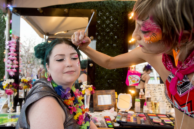 Tabitha Spencer of Boise, Idaho gets her makeup done by Oceana Larsen of Oakland, Calif. on the third night of Electric Daisy Carnival at Las Vegas Motor Speedway on Sunday, June 19, 2016. (Bridge ...