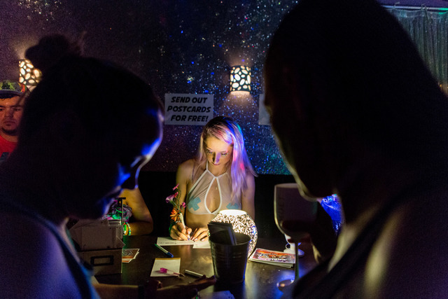 Emily Hildrey writes a post card to her mom and dad at the Post Office in EDC Town on night three a of the Electric Daisy Carnival in the Vegas Motor Speedway Sunday evening, June 19, 2016. (Eliza ...