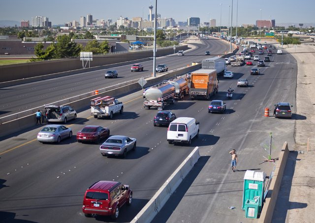 A motorist stops to use a construction port-a-potty in congested traffic on southbound Interstate 15 near downtown Las Vegas as Electric Daisy Carnival festival-goers mingle with the morning commu ...