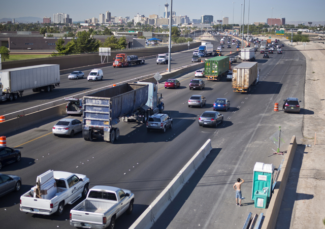 A motorist waits to use a construction port-a-potty in congested traffic on southbound Interstate 15 near downtown Las Vegas as Electric Daisy Carnival festival-goers mingle with the morning commu ...