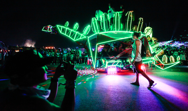 An attendee takes a photo as an art car passes by at Electric Daisy Carnival at the Las Vegas Motor Speedway in Las Vegas during the early hours of Sunday, June 21, 2015. (Chase Stevens/Las Vegas  ...