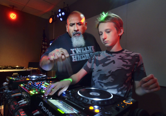 Salvador Avila, branch manager of Las Vegas-Clark County Library District's Enterprise Library, left, works with Nicholas Bower during the Learn to DJ program at the library at 25 E. Shelbourne Av ...