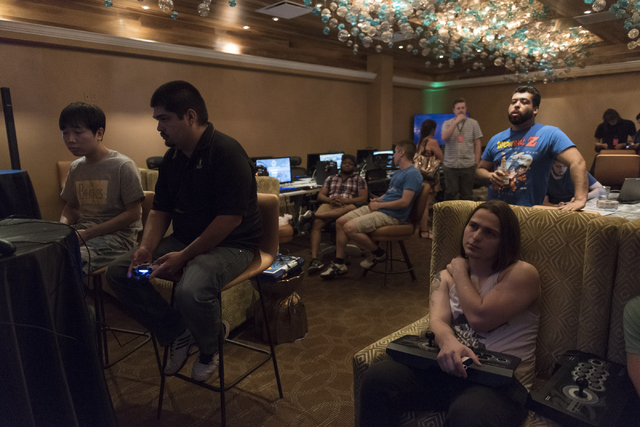 Young Shin, left, and Isaac Perez, second from left,  compete in the Street Fighter V tournament at the Downtown Underground e-sports lounge at Downtown Grand hotel-casino in Las Vegas on Friday,  ...
