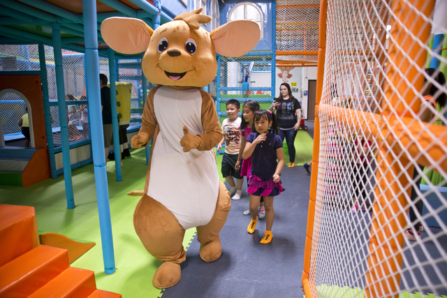 A costumed mascot walks with children inside Kangamoo Indoor Playground May 27, 2016. The playground is one of many in the valley that offer a supervised, climate-controlled space for parents to b ...
