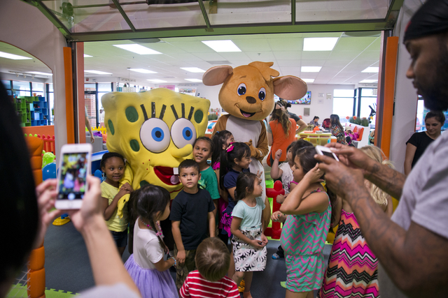 Children pose with costumed visitors inside Kangamoo Indoor Playground located near McCarran Airport on Friday, May 27, 2016. The playground is one of many in the valley that offer a supervised, c ...