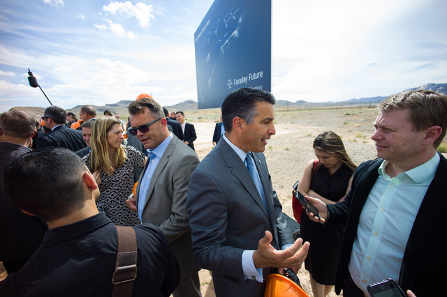 Gov. Brian Sandoval, center right, and Faraday Future Vice President of Manufacturing Dag Reckhorn, center left, speak with reporters following the groundbreaking for Faraday Future's planned 900- ...