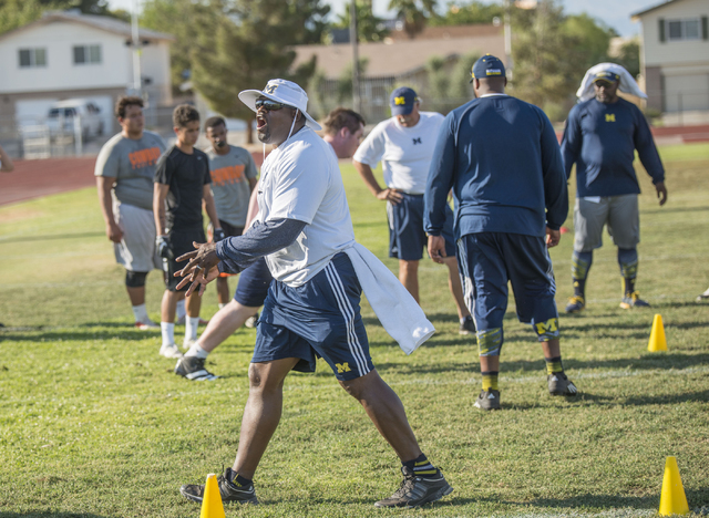 Tyrone Wheatley, running back coach at University of Michigan and former NFL player, coaches participants in the NV Showdown Football Camp at Chaparral High School in Las Vegas on Wednesday, June  ...