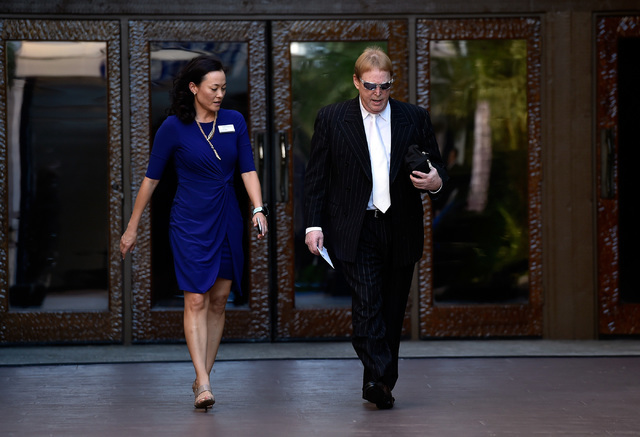 Oakland Raiders owner Mark Davis, right, is escorted by  Kimiko Peterson, Silverton director of advertising, as he arrives at the Gridiron Greats Hall of Fame Induction dinner at the Silverton hot ...