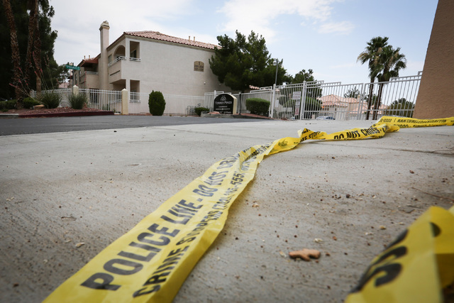 Crime scene tape lies on the ground near the entrance to Torrey Pines Condominiums, where part of a quadruple murder-suicide took place Wednesday night in Las Vegas on Thursday, June 30, 2016. Bre ...