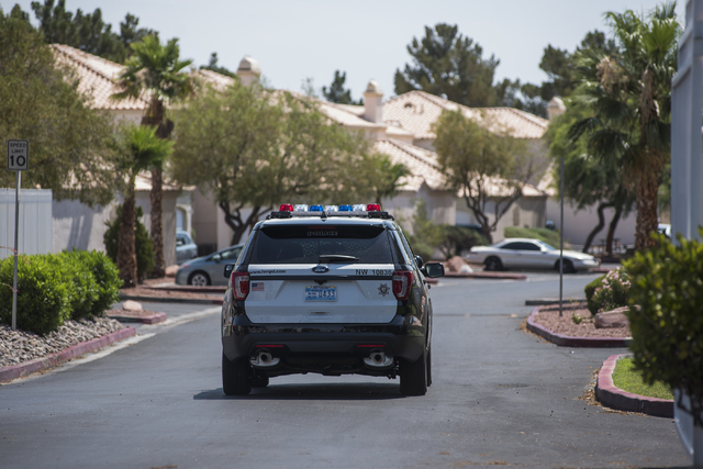 A Las Vegas police officer is seen at Torrey Pines Condominiums in Las Vegas on Thursday, June 30, 2016. Three children were found shot dead in a unit Wednesday night. Police said a man killed his ...
