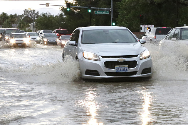 Motorists navigate through a flooded street near Sandhill Road and Russell Road as late afternoon storms move through Las Vegas Valley on Thursday, June 30, 2016. Bizuayehu Tesfaye/Las Vegas Revie ...