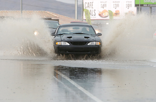 Motorists navigate through a flooded street near Russell Road and Whitney Ranch in Henderson as late afternoon storms move through Las Vegas Valley on Thursday, June 30, 2016. (Bizuayehu Tesfaye/L ...