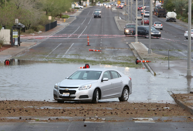 A disabled vehicle sits on Pecos Road near Robindale Road and Windmill Parkway in Henderson due to flooding as late afternoon storms move through Las Vegas Valley on Thursday, June 30, 2016. (Bizu ...