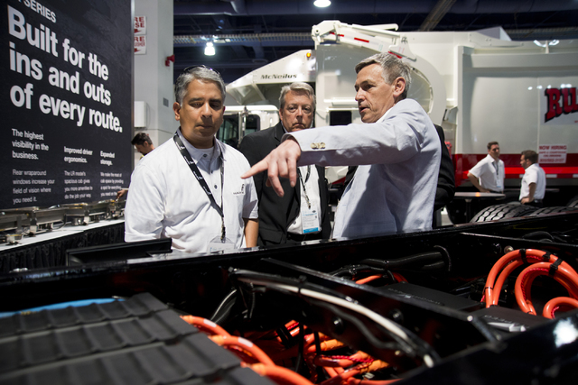 Ian Wright, right, explains the features on a Mack Trucks LR Model fitted with an energy efficient Wrightspeed Powertrain Route 1000 electric drive system at the Waste Expo inside the Las Vegas Co ...