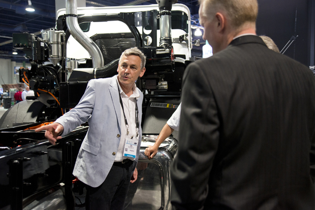 Ian Wright, left, explains the features on a Mack Trucks LR Model fitted with an energy efficient Wrightspeed Powertrain Route 1000 electric drive system at the Waste Expo inside the Las Vegas Con ...
