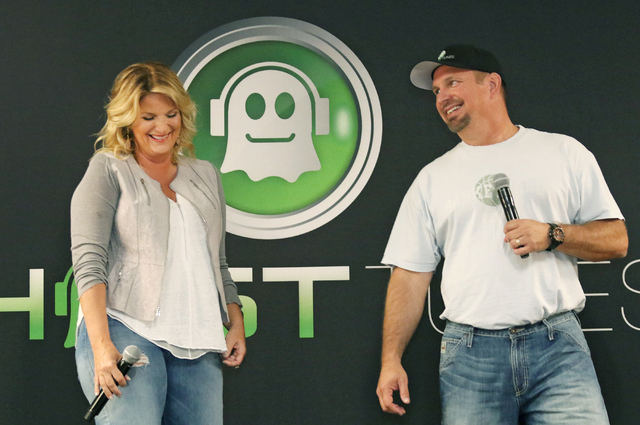 Country music star Garth Brooks, right, smiles at wife and fellow performer Trisha Yearwood while answering questions about the duo's Garth Brooks World Tour with Trisha Yearwood during a news con ...