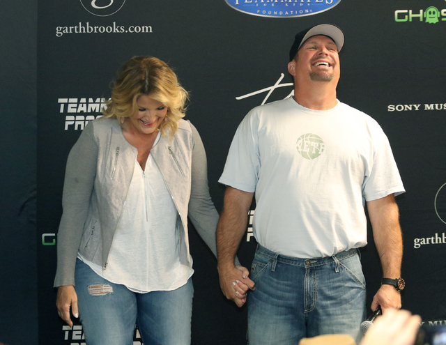 Country music star Garth Brooks, right, shares a laugh with wife and fellow performer Trisha Yearwood during a news conference at T-Mobile Arena Friday, June 24, 2016, in Las Vegas. (Ronda Churchi ...
