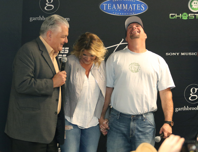Country music star Garth Brooks, from right, shares a laugh with wife and fellow performer Trisha Yearwood while Clark County Commission Chairman Steve Sisolak leads a news conference at T-Mobile  ...