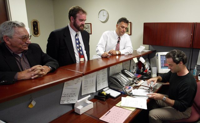 Chuck Patti, left, and Christopher Hansen, center, look on as political activist Tony Dane files paperwork with administrative assistant Jeff Fuell, right, Aug. 26, 2003. Dane and others are attem ...
