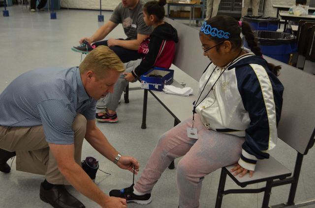 Las Vegas Southwest Rotary Club President Mitchell Horst helps fit a Ferron Elementary School student with new shoes during a Happy Feet distribution event May 17, 2016. Ginger Meurer/Special to View