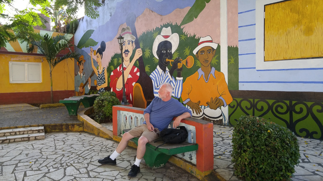 Dr. Joe Iser, sits in a square were mural artists worked. (Courtesy/Gabriel and Joel Mark)