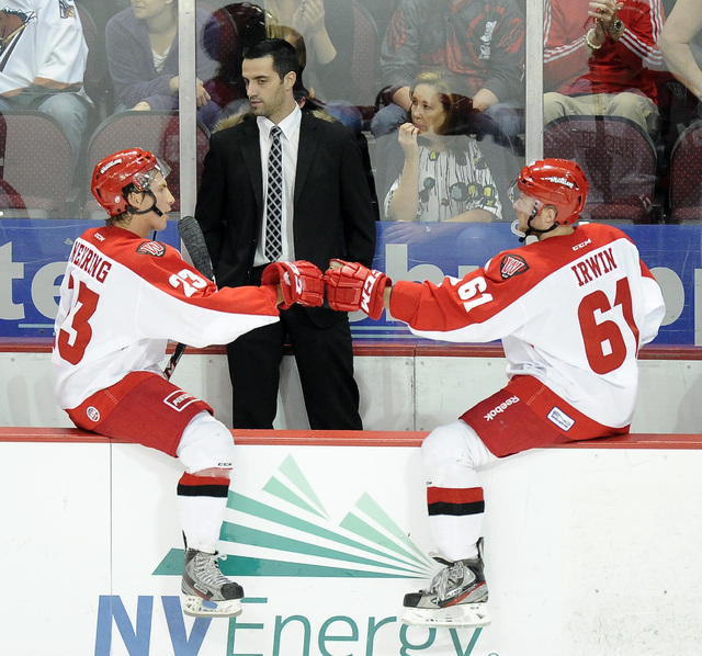 Las Vegas Wranglers forward Geoff Irwin (61) and center Chad Nehring (23) high five each other in front of head coach Mike Madill in the second period of an ECHL hockey game against the Utah Grizz ...