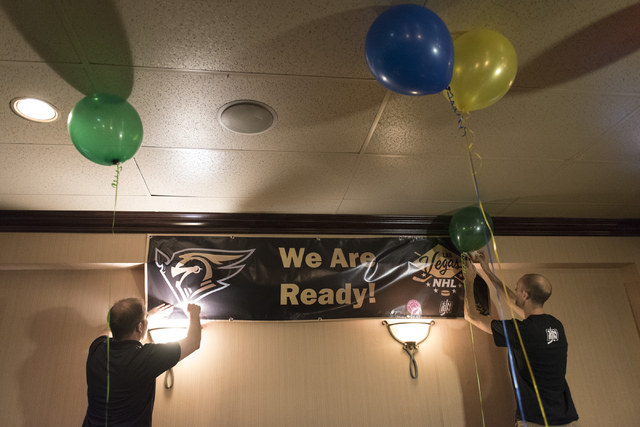 Eric Biro, left, and Ken Boehlke hang a hockey banner at O'Aces Bar & Grill following a conference in which the NHL's Board of Governors approved an expansion franchise in Las Vegas Wednesday, ...