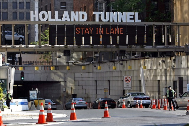 Police officers stand by as New Jersey-bound traffic streams into the New York entrance of the Holland Tunnel Friday, July 7, 2006 in New York. (Jason DeCrow/AP)