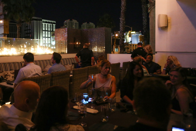 Spectators dine at a watch party for the implosion of a Riviera hotel tower, seen top left, at the Barrymore in Las Vegas on Tuesday, June 14, 2016. Brett Le Blanc/Las Vegas Review-Journal Follow  ...