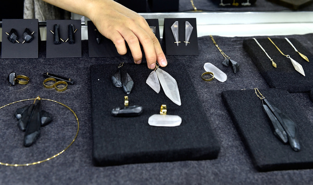 """Olivia Shin adjust her """"Black Gold"""" collection at her booth at the JCK Las Vegas jewelry industry show at the Mandalay Bay Convention Center Friday, June 3, 2016, in Las Vegas. D ..."""
