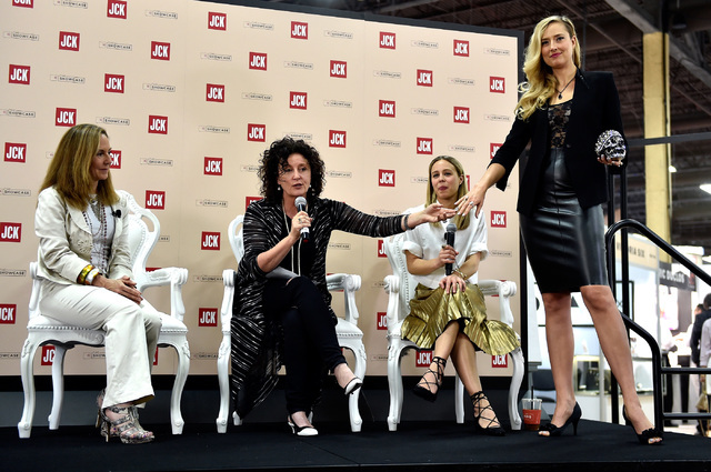 Panelist from left, Karen Gilberson, costume designer Lyn Paolo and fashion editor Shannon Adducci talk of trends of jewelry as model Alexandra Zevalking displays rings at the JCK Las Vegas jewelr ...