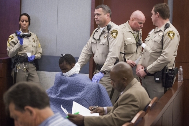 A wheel chair bound Kahleal Black, charged in the officer-involved shooting in front of the Bellagio fountains on Friday, makes his initial court appearance at Regional Justice Center on Wednesday ...