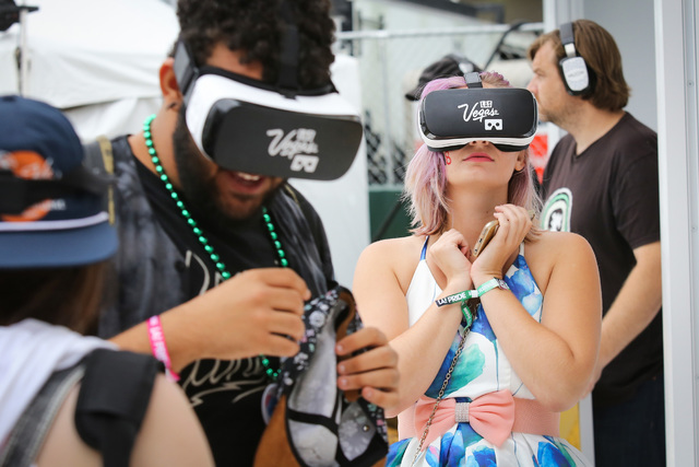 Carolyn Darlin, right, a 26-year-old that lives in Los Angeles, and Caleb Smith, center, a 19-year-old from Wynne, Ark., take virtual reality tours of Las Vegas at the Los Angeles Pride Festival o ...