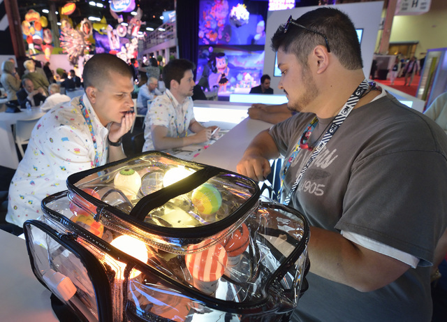 Mark McCoy, licensing manager for HueVee, a company making custom-branded LED light bulbs, right, talks with Mark Putnam, Cartoon Network marketing manager, during the Licensing Expo at the Mandal ...