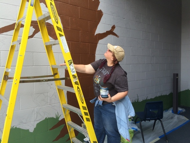 Celestia Ward gets ready to ascend a ladder May 20, 2016, at Leavitt Middle School, 4701 Quadrel St., as she paints the artwork developed from students' input. Jan Hogan/View